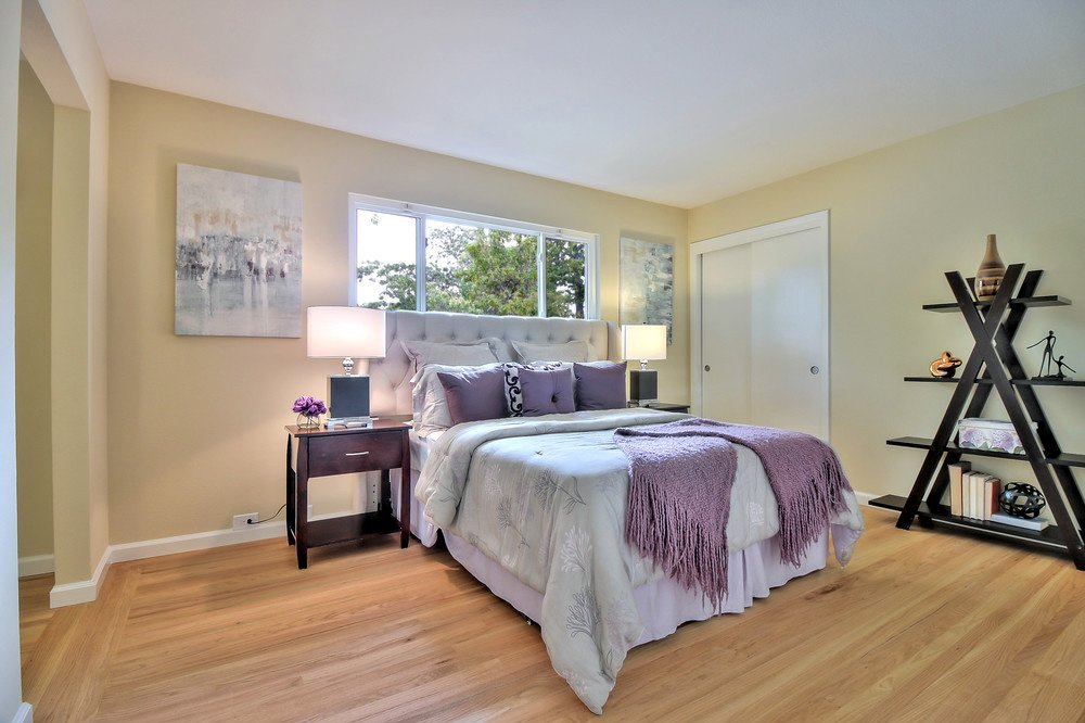 A bedroom after cleanup: note newly painted walls and new wood flooring