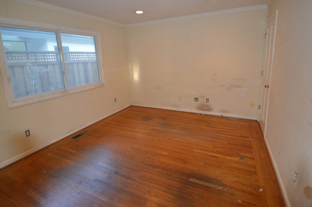 Bedroom before cleanup: note stains on wall and floor