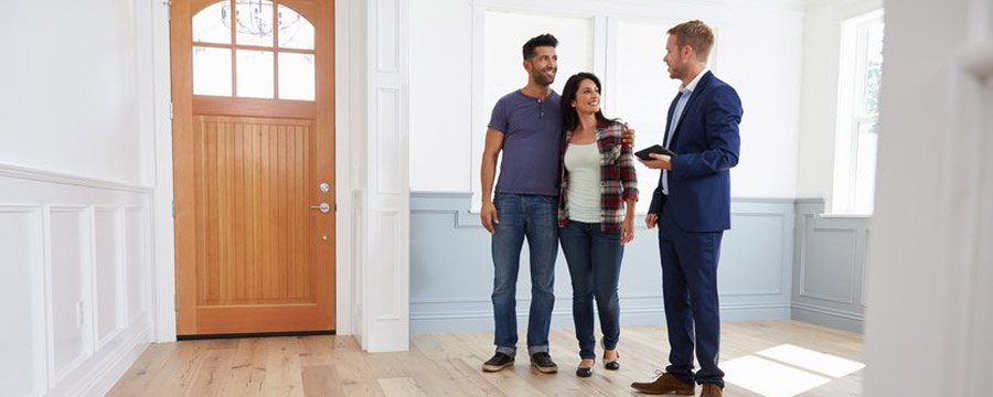Couple and real estate agent talking together while visiting the interior of a home for sale